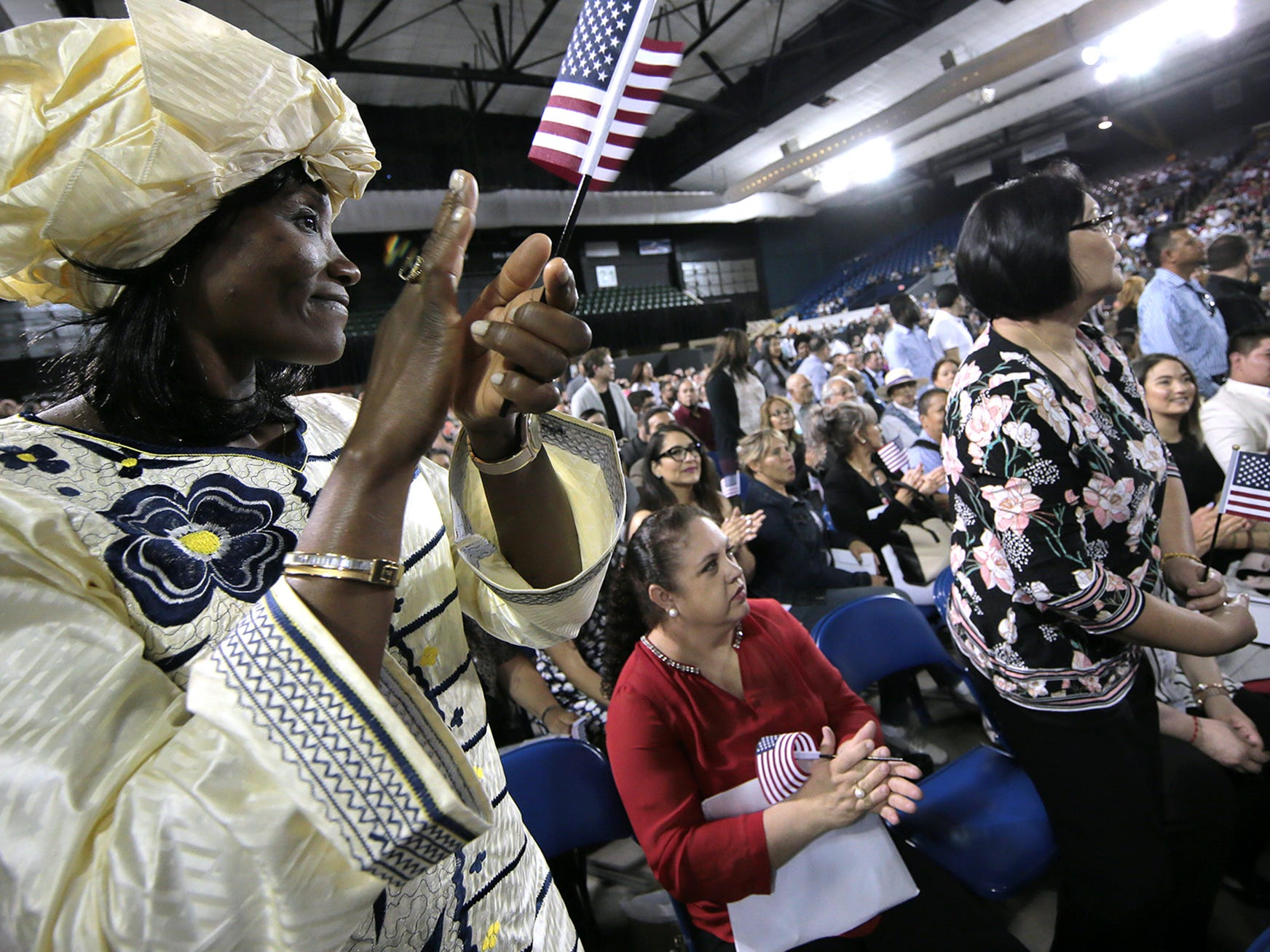 Leonie Tegnoche of Cameroon claps as her country was announced at a citizenship ceremony for 740 new citizens Thursday at the El Paso County Coliseum.