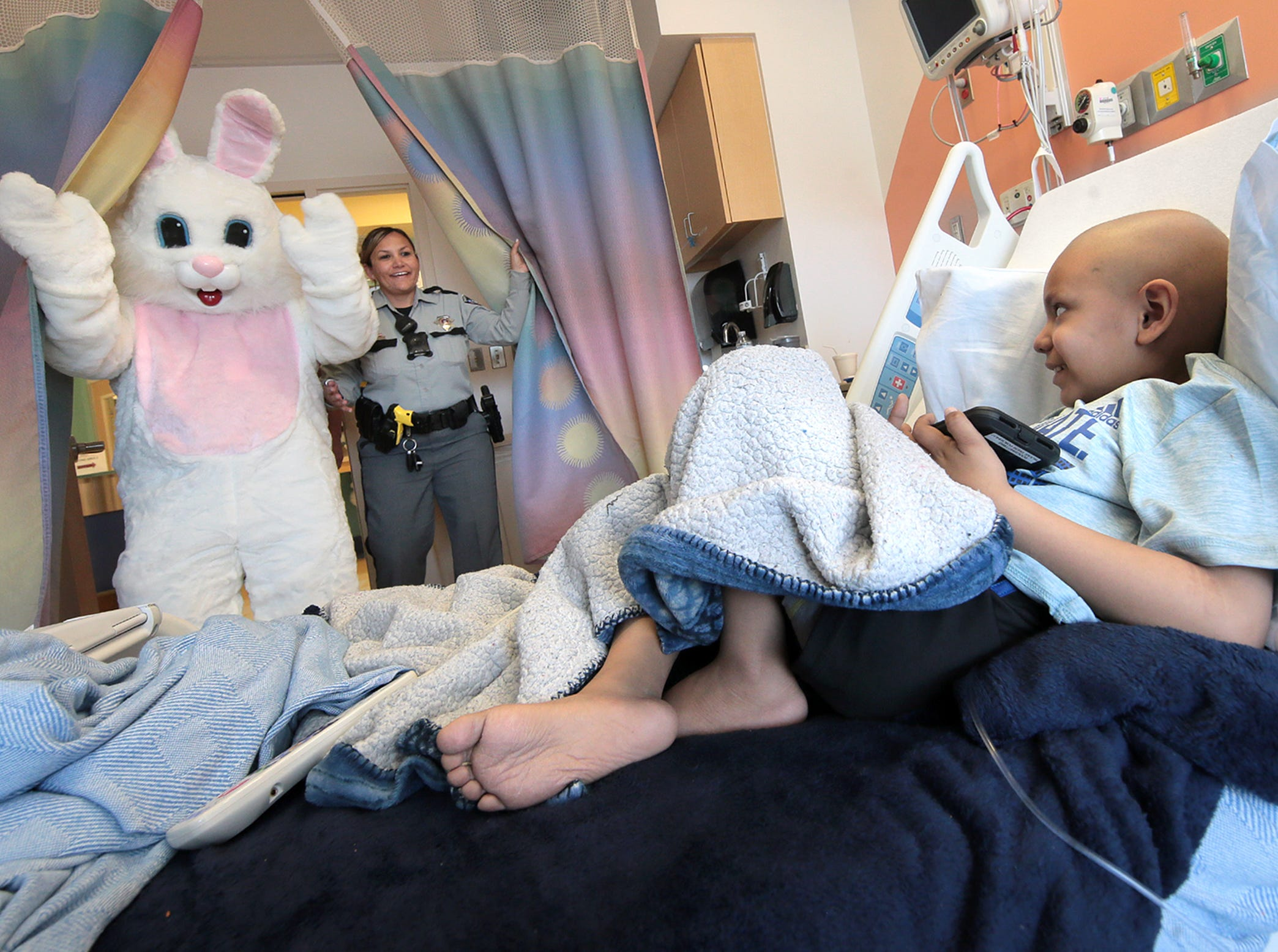 Deputy Josie Ramirez and the Easter Bunny visit 5-year-old Esteban Lerma and the other kids at El Paso Children's Hospital on Thursday afternoon, April 18, 2019. Sheriff Richard Wiles joined the Easter Bunny in delivering gifts to children who will be in the hospital over the Easter weekend.