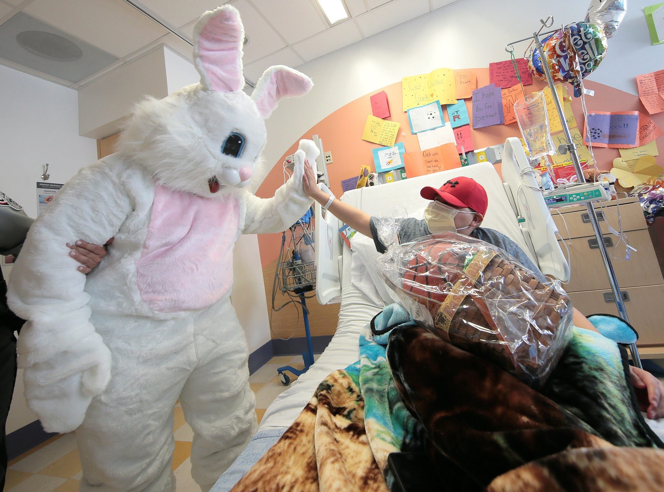 Frank Gonzalez, 12, a patient at El Paso Children's Hospital, high fives the Easter Bunny who was visiting children with El Paso County Sheriff Richard Wiles Thursday.