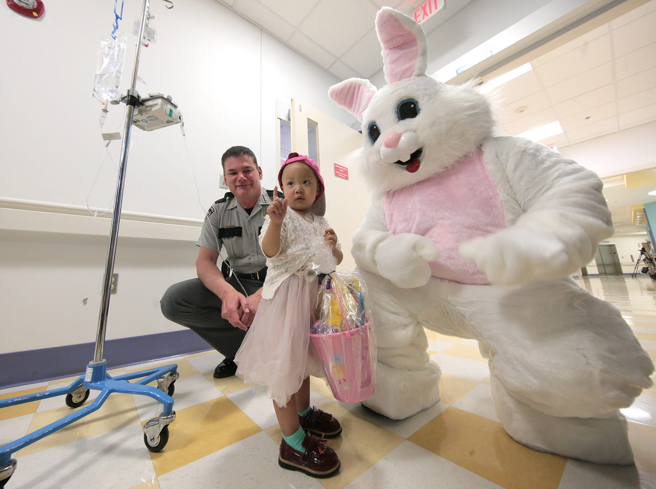 El Paso Children's Hospital patient Nicole Liu, 2, is given an Easter basket from El Paso County Sheriff Richard Wiles and the Easter Bunny Thursday.