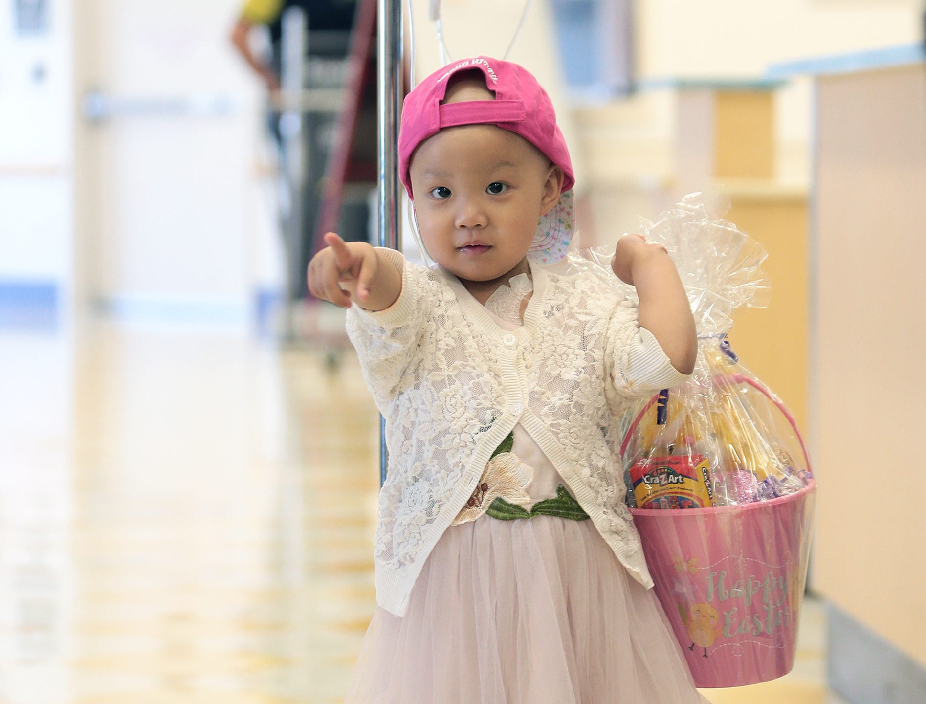 Nicole Liu, 2, points to the Easter Bunny, who had just given her an Easter Basket on Thursday, April 18, 2019, at El Paso Children's Hospital. The Easter Bunny visited children at the hospital, along with El Paso Sheriff Richard Wiles and several deputies. Nicole followed the Easter Bunny on his entire visit at the hospital.
