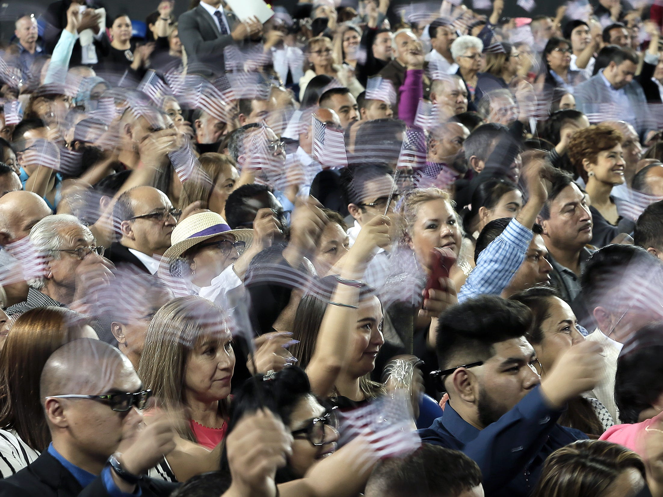 New citizens wave their flags after taking the oath of citizenship Thursday at the El Paso County Coliseum.
