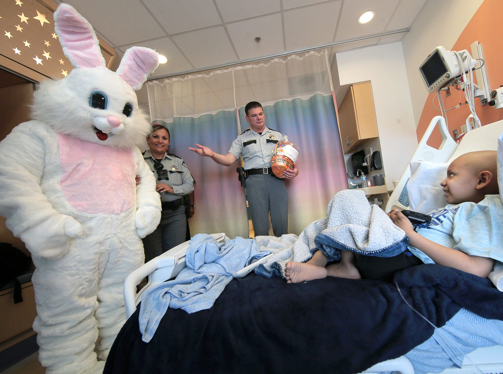 El Paso County Sheriff Richard Wiles and the Easter Bunny visit five-year-old Esteban Lerma in his roon at El Paso Children's Hospital Thursday delivering Easter baskets and smiles to kids who will be in the hospital over the Easter weekend.
