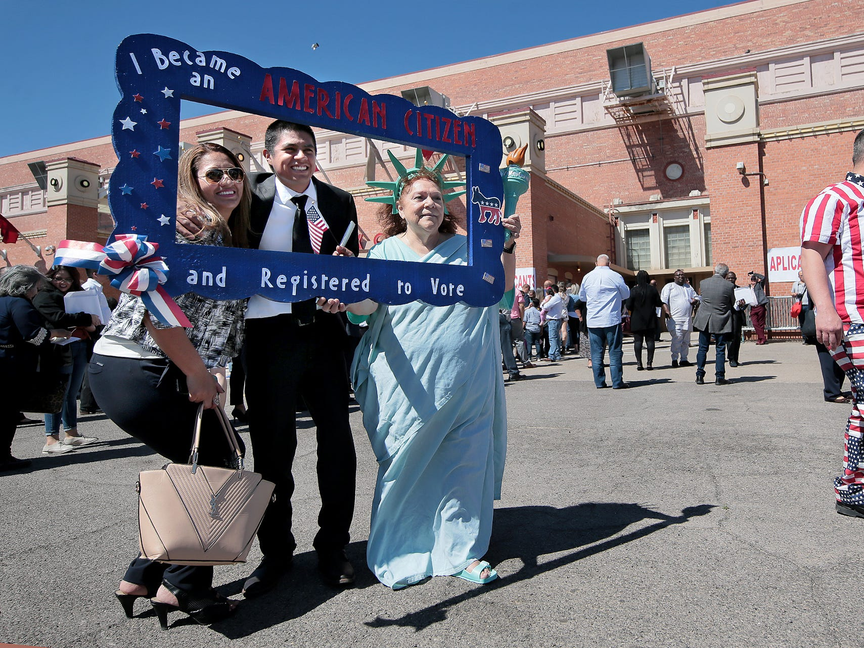 Ceci Carpio takes photos with new citizens after the ceremony Thursday at the El Paso County Coliseum.