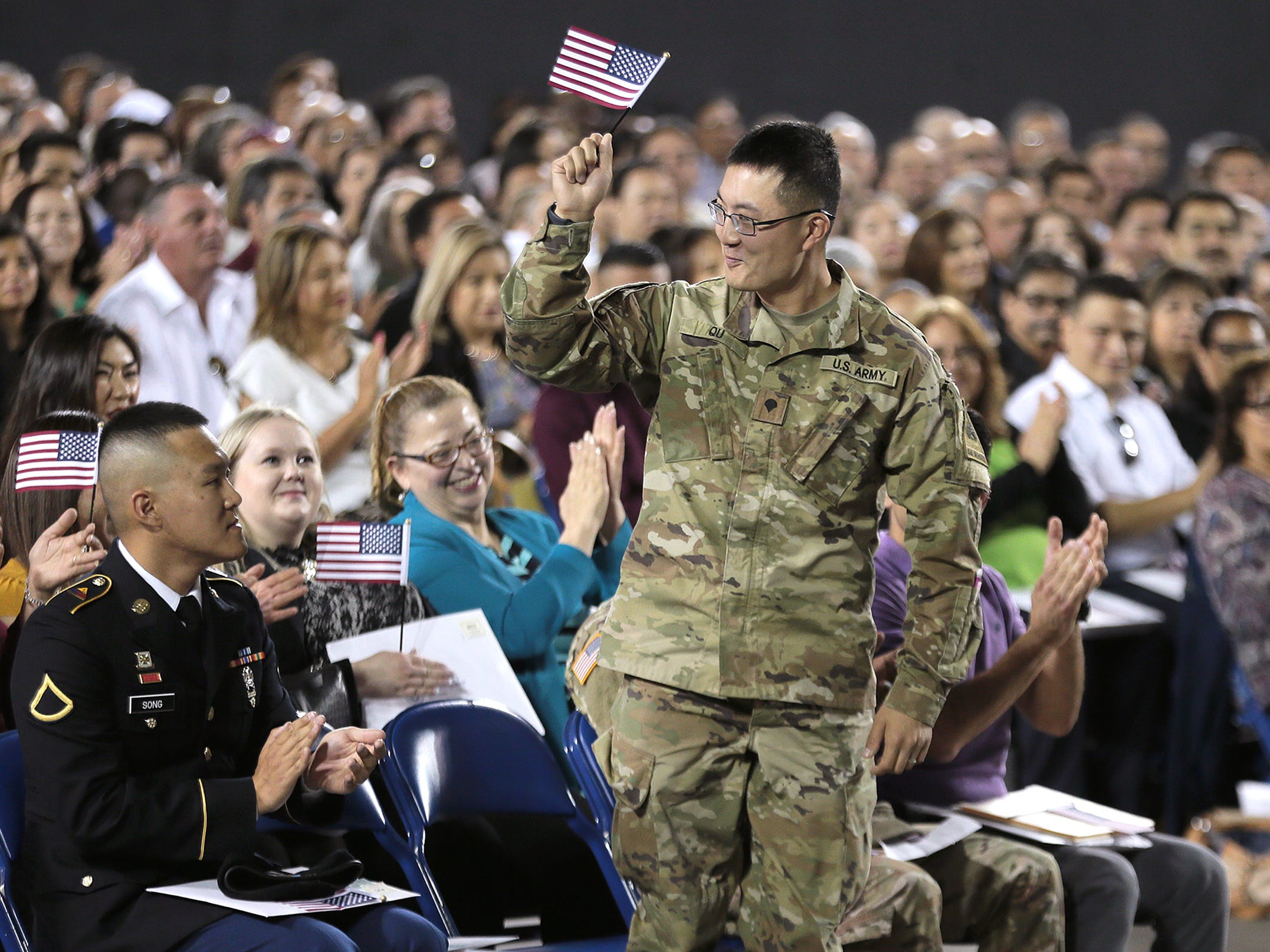 Zhan Qu of the 1st Armored Division Band at Fort Bliss acknowledges the crowd after being introduced at a citizenship ceremony Thursday for 740 people at the El Paso County Coliseum. U.S. District Judge David C. Guaderrama administered the oath of citizenship.