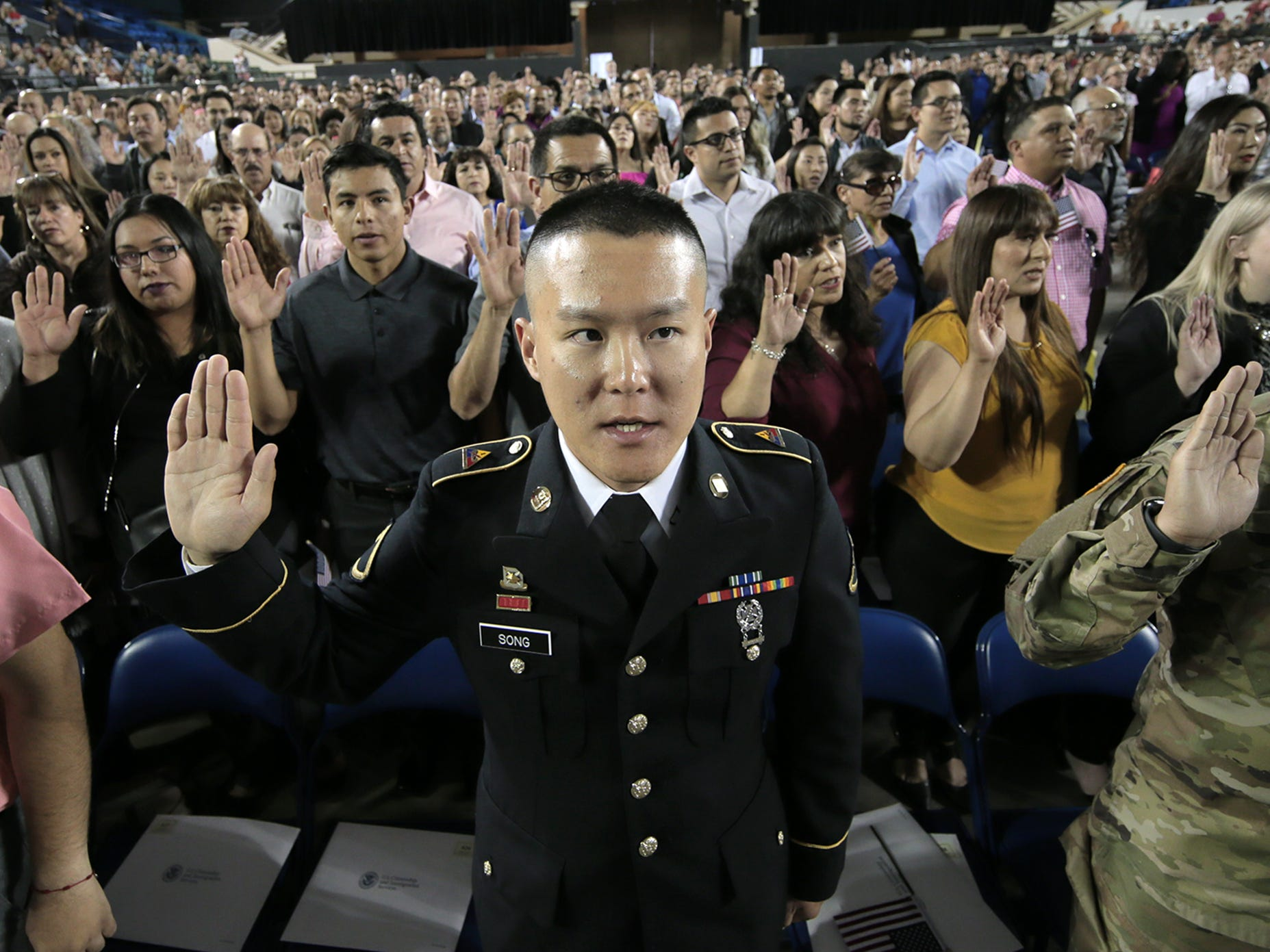 Kyeongjin Song of Korea takes the oath of citizenship Thursday along with 739 other new citizens at the El Paso County Coliseum.