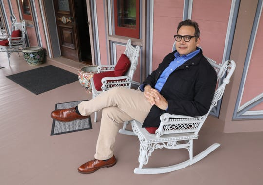Michael Hall Lombardi, sits on the porch of the Armour-Stiner (Octagon) House in Irvington, April 18, 2019. This unique home, a house museum on the National Register of Historic Places, is now open to visitors.