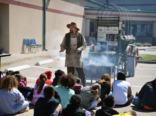 Bill Emrick of Archer City demonstrated chuckwagon cooking for groups of fourth graders during Texas Living History Day at Region 9 Education Service Center Thursday morning.