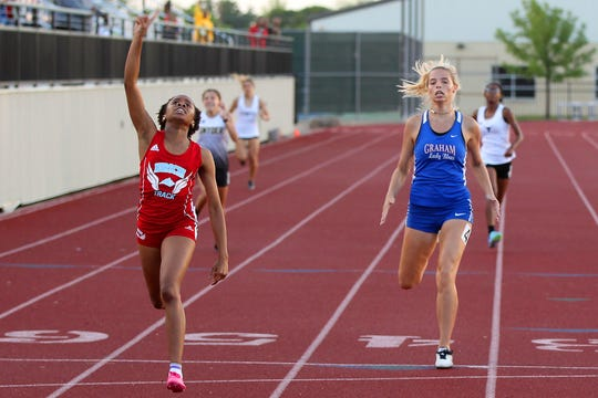 Ashton Carter of Hirschi celebrates the win and Graham's Rosemary Schaffer takes second in the 400 Wednesday.