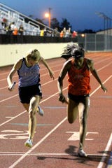 Midland Greenwood (left) beats out Burkburnett's Tania Lee in a photo finish in the women's mile relay Wednesday at the 5/6-4A Area Meet.