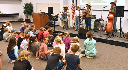 The Camp Cookie Trio performs traditional trail songs for a group of fourth grade students Thursday during Texas Living History Day at Region 9 Education Service Center.