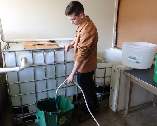 Junior Caleb Dille of the Coshoton County Career Center fills containers with water to sit overnight before being added to the aquaponics garden. Fish waste is circulated to a grow bed of pea gravel for lettuce. Water with nitrogen fixating bacteria then goes from the garden back to the fish tank.