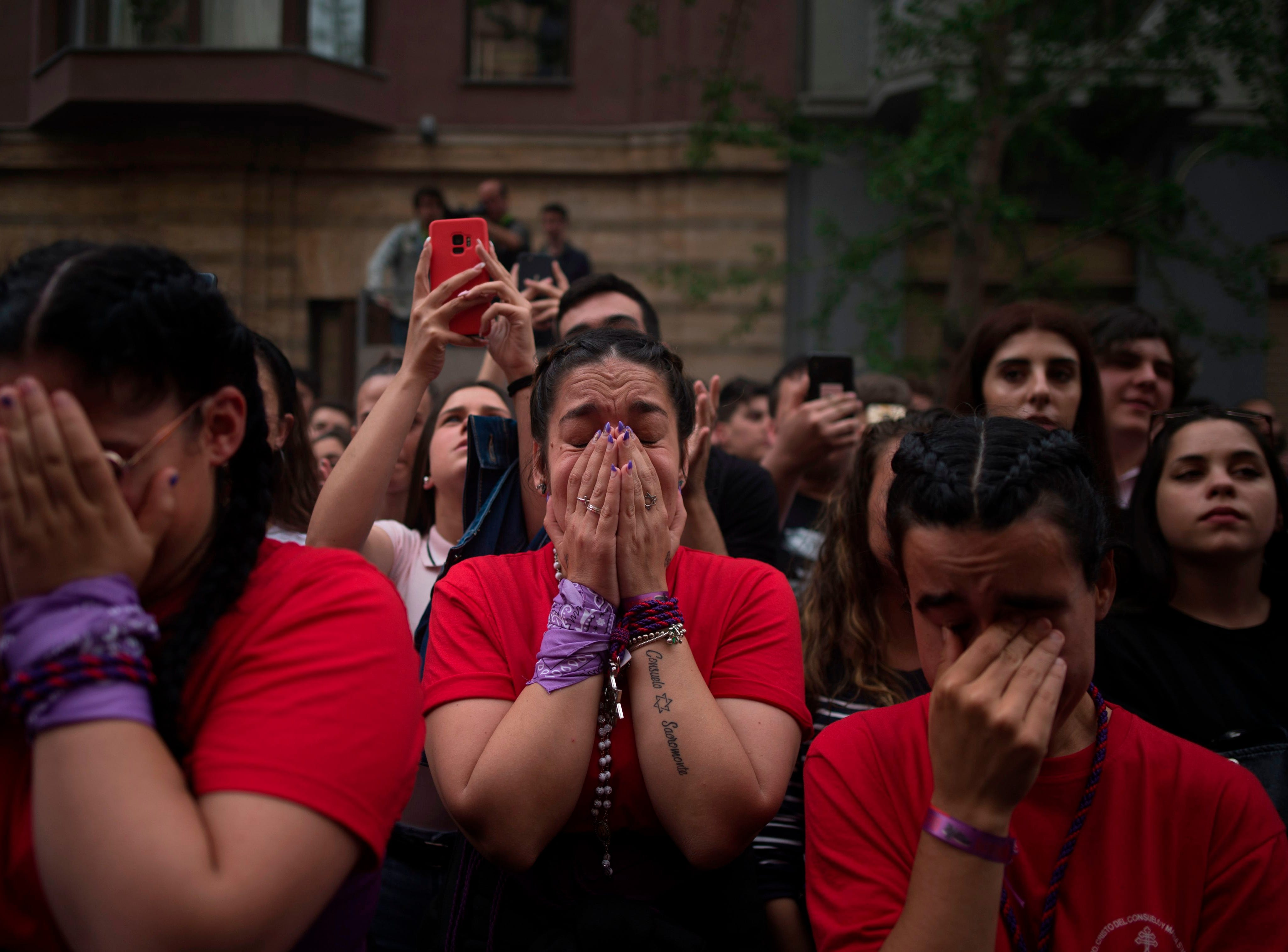 """Penitents cry during the """"Cristo de los Gitanos"""" (The Gypsy) brotherhood Easter procession in Granada on April 17, 2019. Christian believers around the world mark the Holy Week of Easter in celebration of the crucifixion and resurrection of Jesus Christ."""