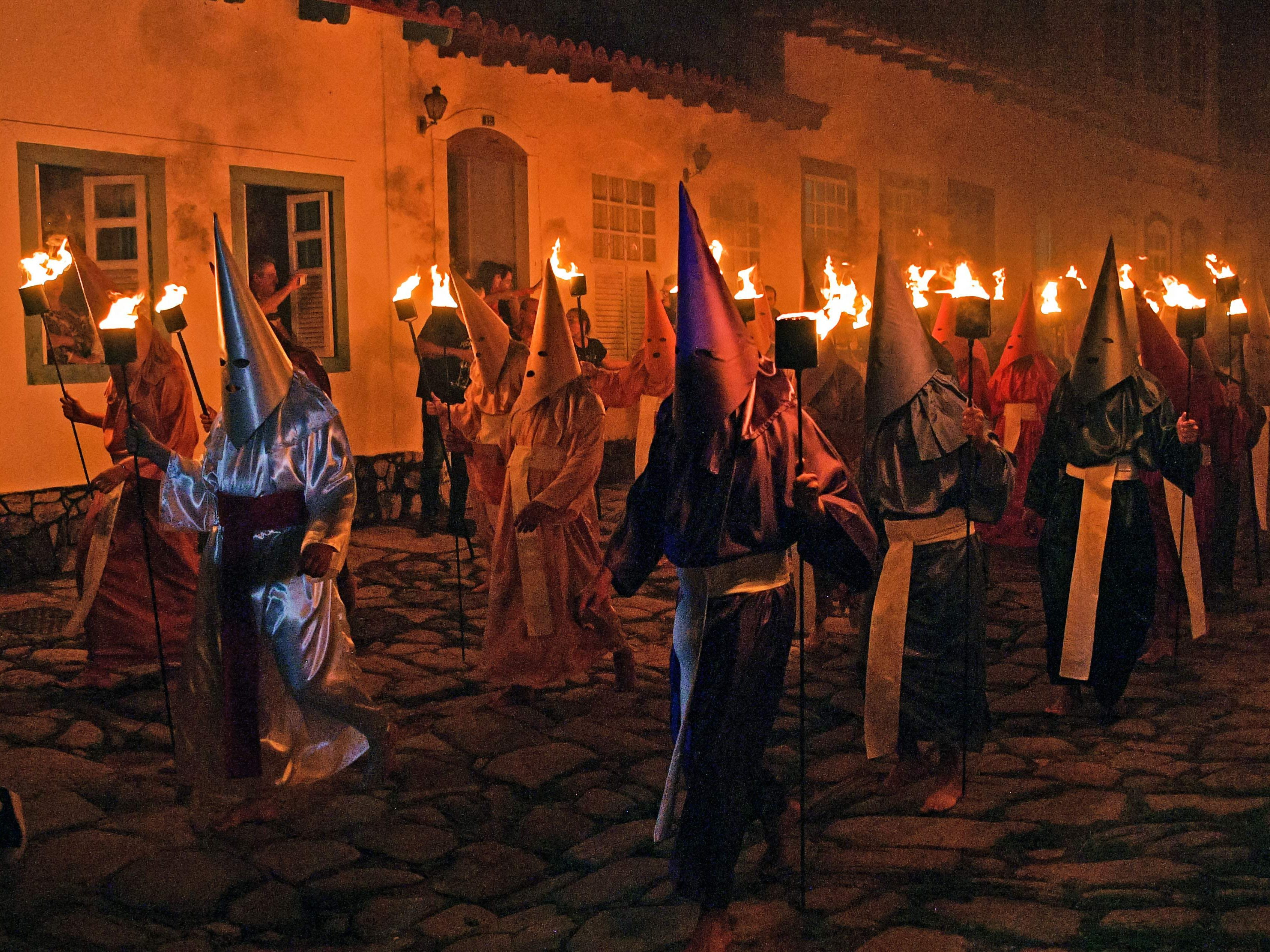 """Hooded catholic faithful representing Roman soldiers, known as """"Farricocos"""", carry flaming torches during the annual Fogareu Holy Week procession in Goias, 350 km west of Brasilia, Brazil, on April 17, 2019. The Christian religious ceremony is a re-enactment of the arrest of Jesus Christ. The costumes are of medieval origin, and were used by penitents so they could atone for their sins without having to reveal their identity in public."""