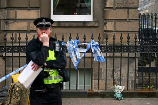 "Flowers are placed at a location from ""T2 Trainspotting"" in memory of boxer-turned-actor Bradley Welsh, who was fatally shot Wednesday near his home in Edinburgh, Scotland."