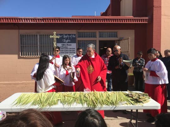 The Rev. Antonio Lasheras blesses the palm fronds before the start of Palm Sunday Mass April 14 outside of Our Lady of the Light Catholic church in El Paso, Texas. For the 100-plus parishioners, the day marked the joyous return of Jesus into Jerusalem before his crucifixion on Good Friday.