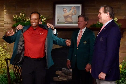 Tiger Woods receives the green jacket from Patrick Reed in the Butler Cabin as Augusta National chairman Fred Ridley and CBS announcer Jim Nantz look on.