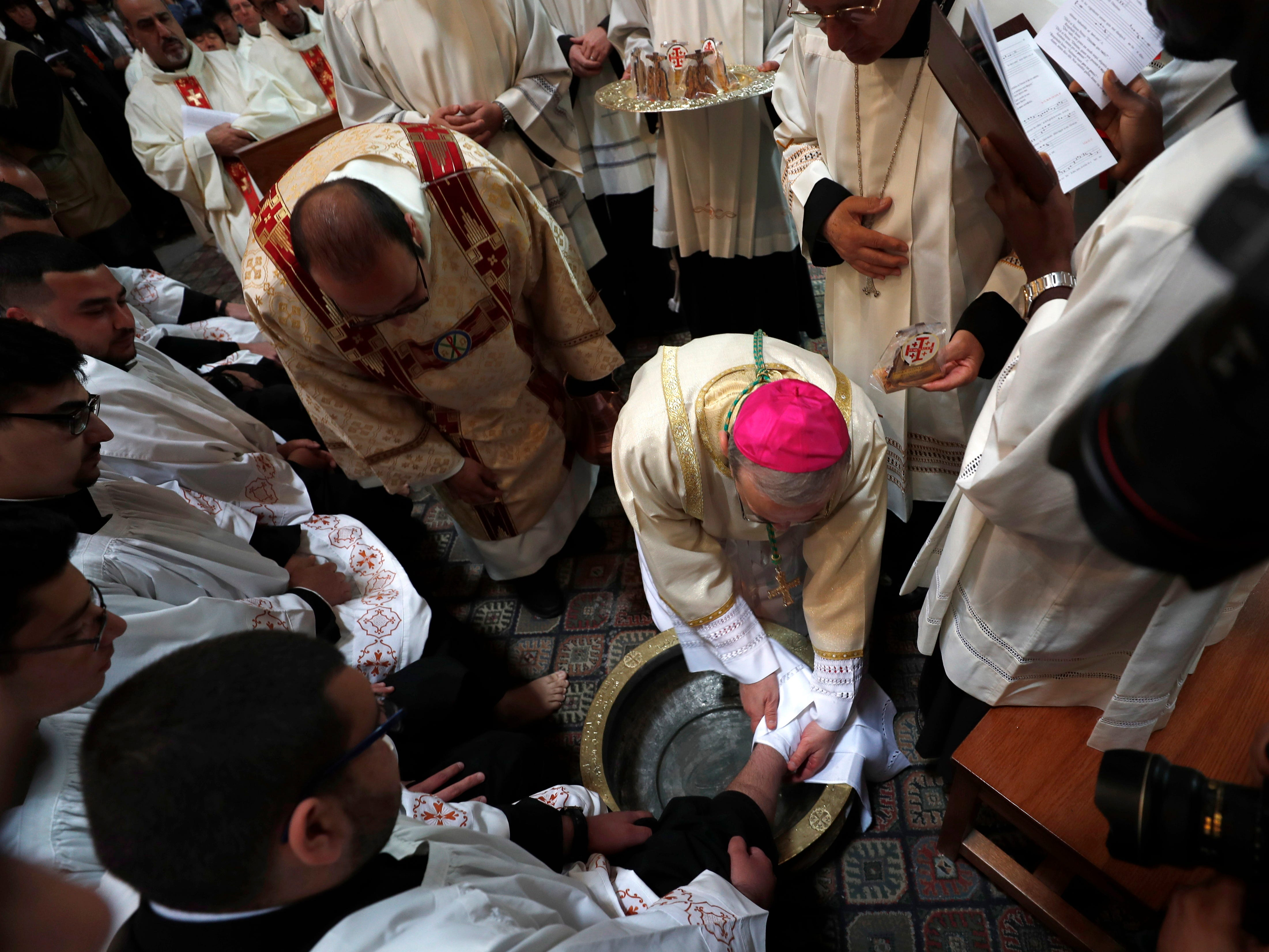 Pierbattista Pizzaballa, Latin Patriarchate of Jerusalem, washes a foot as he leads the procession of the holy Thursday, during the Catholic Washing of the Feet ceremony on Easter Holy Week, at the Church of the Holy Sepulcher in Jerusalem's old city on April 18, 2019.