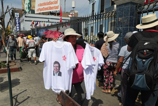 A woman sells T-shirts featuring Peru's late President Alan Garcia outside his political party's headquarters where his wake takes place in Lima, Peru,  April 18, 2019. Garcia shot himself in the head and died Wednesday as officers waited to arrest him in a massive graft probe that has put the country's most prominent politicians behind bars and provoked a reckoning over corruption.