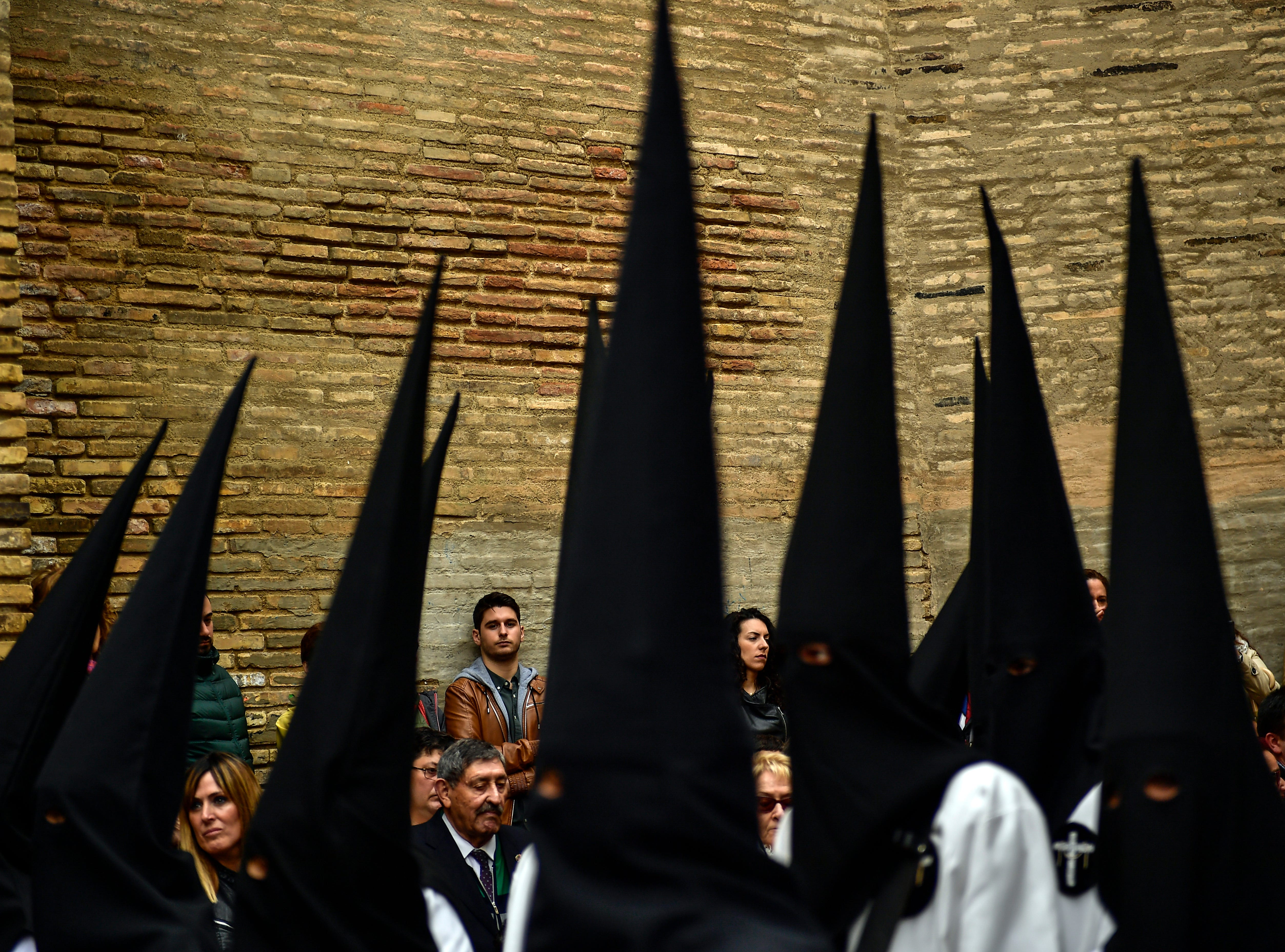 Hooded penitents from the ''Exaltacion de La Santa Cruz'' brotherhood take part in a Holy Week procession in Zaragoza, northern Spain, Thursday, April 18, 2019.
