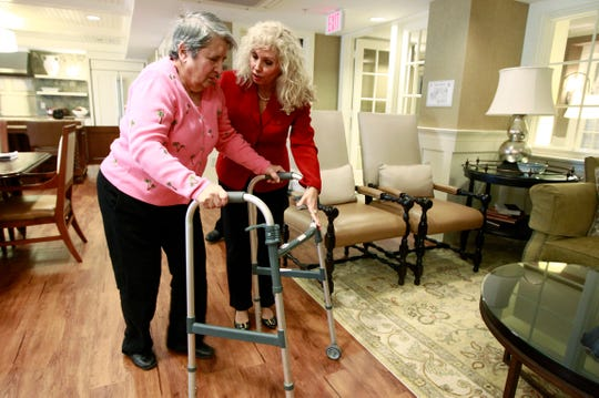 Alexis McKenzie, executive director of The Methodist Home of the District of Columbia Forest Side, an Alzheimer's assisted-living facility, walks with resident Catherine Peake, in Washington, Monday, Feb. 6, 2012. A Place for Mom, a senior living referral service, released its 2018 senior living cost index on Tuesday, April 23, 2019.