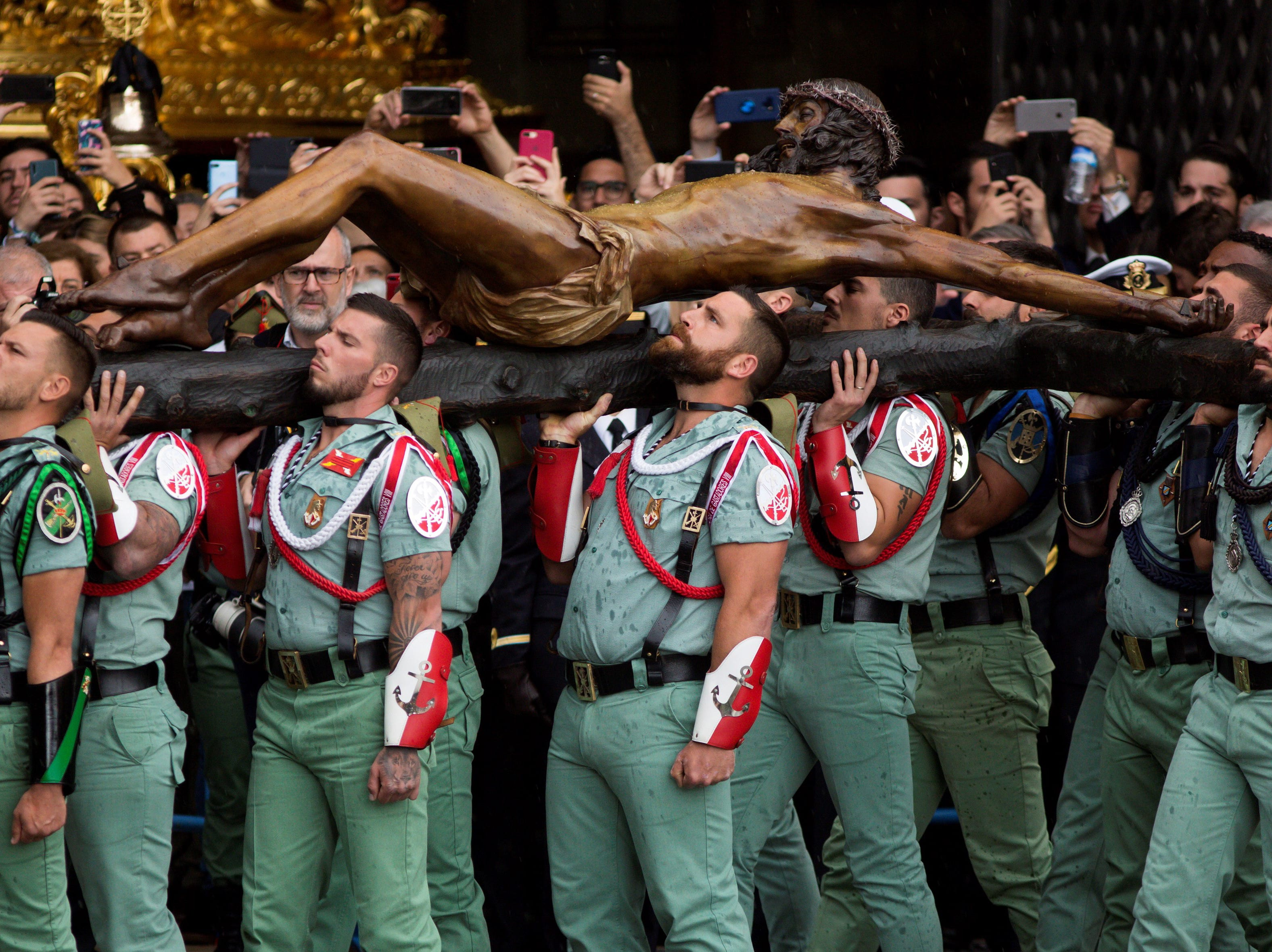 Legionaries carry the Christ of the Good Death in preparation for its procession in Malaga, Spain on April 18, 2019. Legionaries carry the Christ to its 'throne' before the start of the procession later in the day.