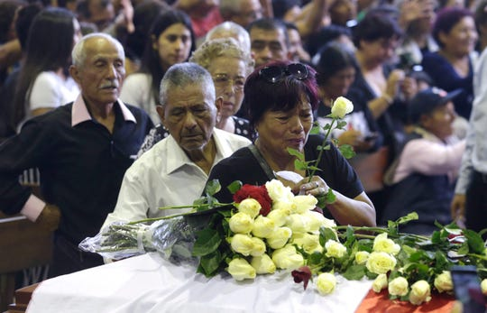 A supporter of Peru's late President Alan Garcia puts a flower on his coffin on the second day of his wake at his party's headquarters in Lima, Peru, April 18, 2019. Garcia shot himself in the head and died Wednesday as officers waited to arrest him in a massive graft probe that has put the country's most prominent politicians behind bars and provoked a reckoning over corruption.