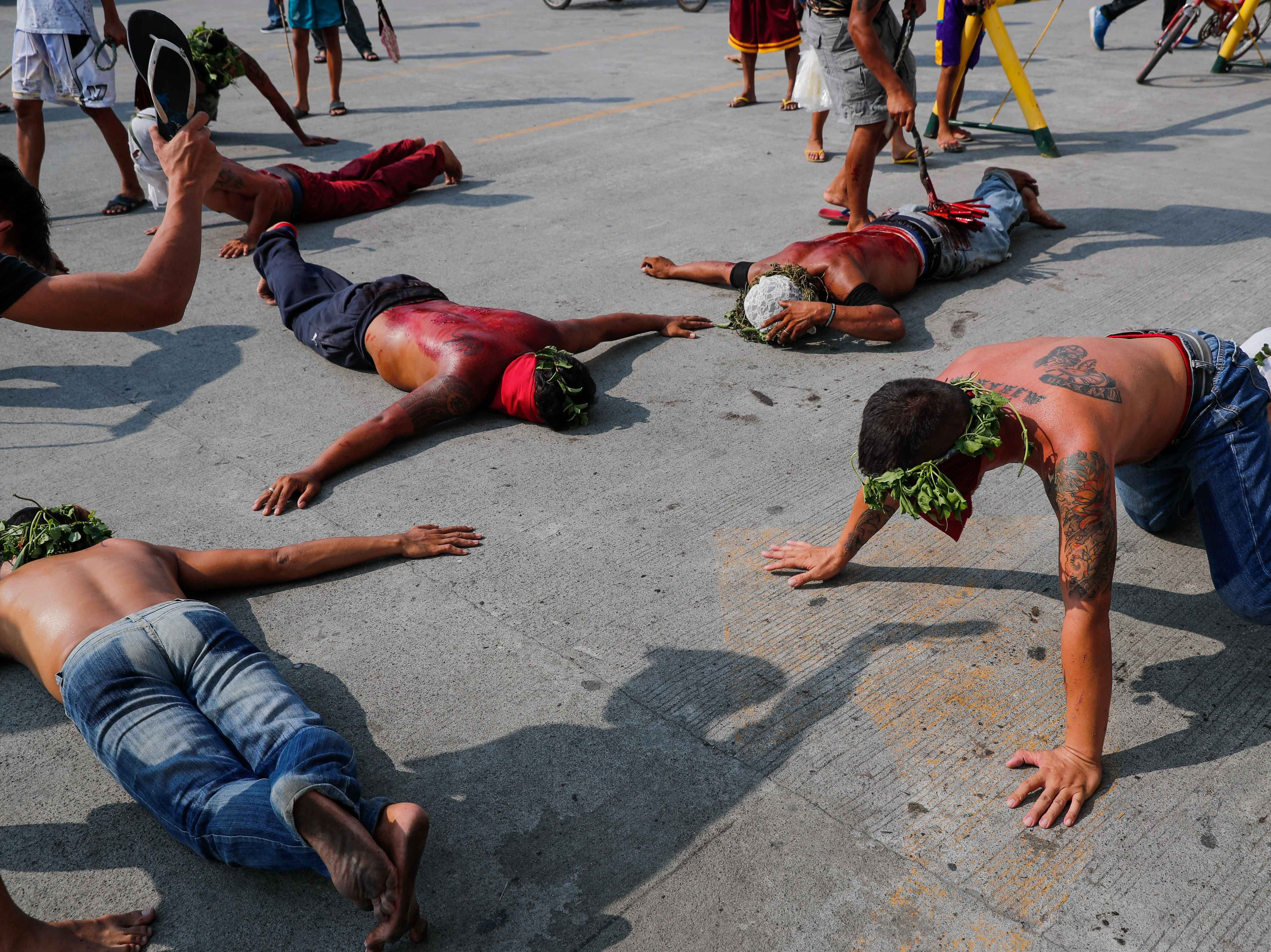 Flagellants are whipped in front of a church on Maundy Thursday in San Fernando, Pampanga province, Philippines on April 18, 2019. Many Filipino Catholic penitents mark the Holy Week by submitting to different forms of physical penance in the hopes of being forgiven for their sins.