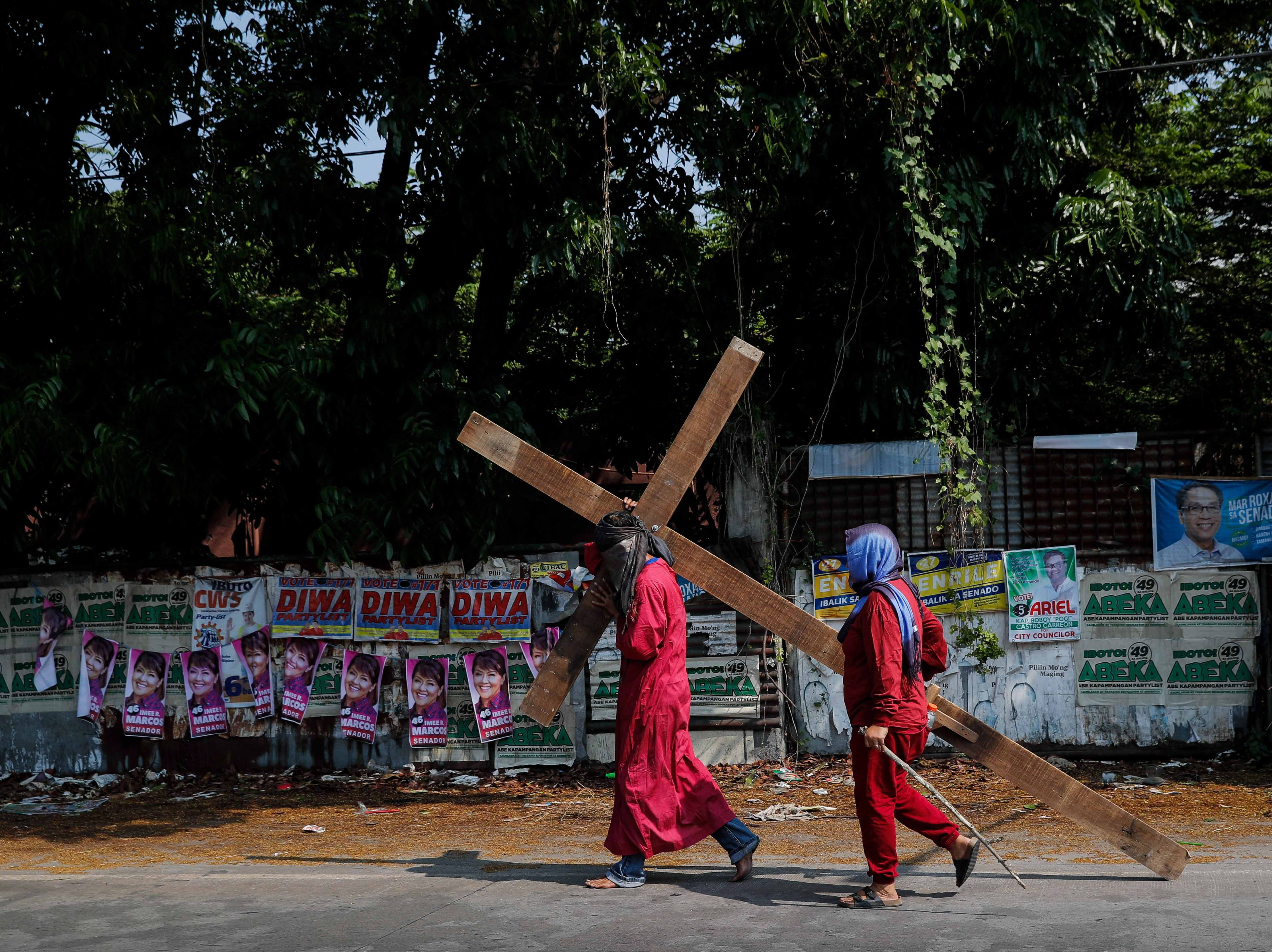 A flagellant carries a wooden cross along campaign posters on Maundy Thursday in San Fernando, Pampanga province, Philippines on April 18, 2019. Many Filipino Catholic penitents mark the Holy Week by submitting to different forms of physical penance in the hopes of being forgiven for their sins.
