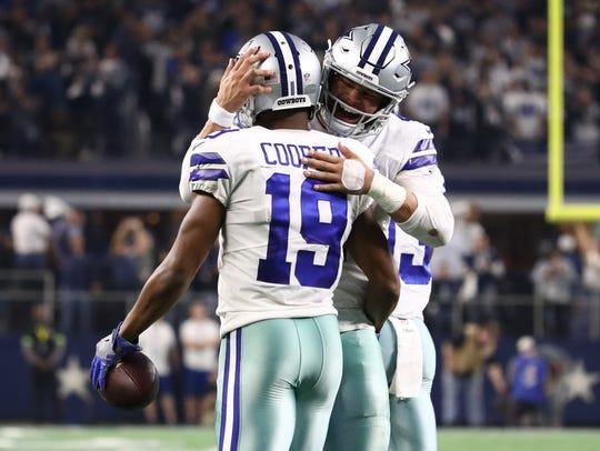 Cowboys receiver Amari Cooper and quarterback Dak Prescott celebrate a touchdown.