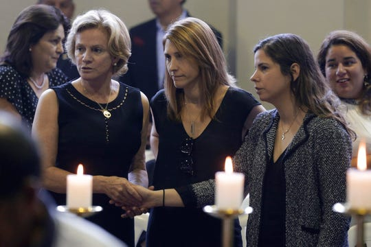 Pilar Nores, ex-wife of Peru's late President Alan Garcia, left, and their daughters, Josefina, center, and Luciana attend Garcia's wake at his party's headquarters in Lima, Peru, April 18, 2019. Garcia shot himself in the head and died Wednesday as officers waited to arrest him in a massive graft probe that has put the country's most prominent politicians behind bars and provoked a reckoning over corruption.