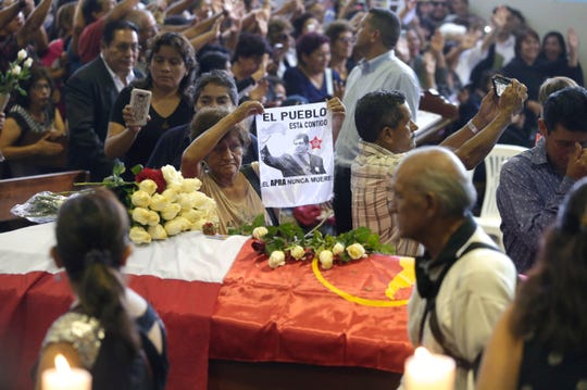 A woman holds up an image of Peru's late President Alan Garcia next to his coffin on the second day of his wake at his party's headquarters in Lima, Peru, April 18, 2019. Garcia shot himself in the head and died Wednesday as officers waited to arrest him in a massive graft probe that has put the country's most prominent politicians behind bars and provoked a reckoning over corruption.