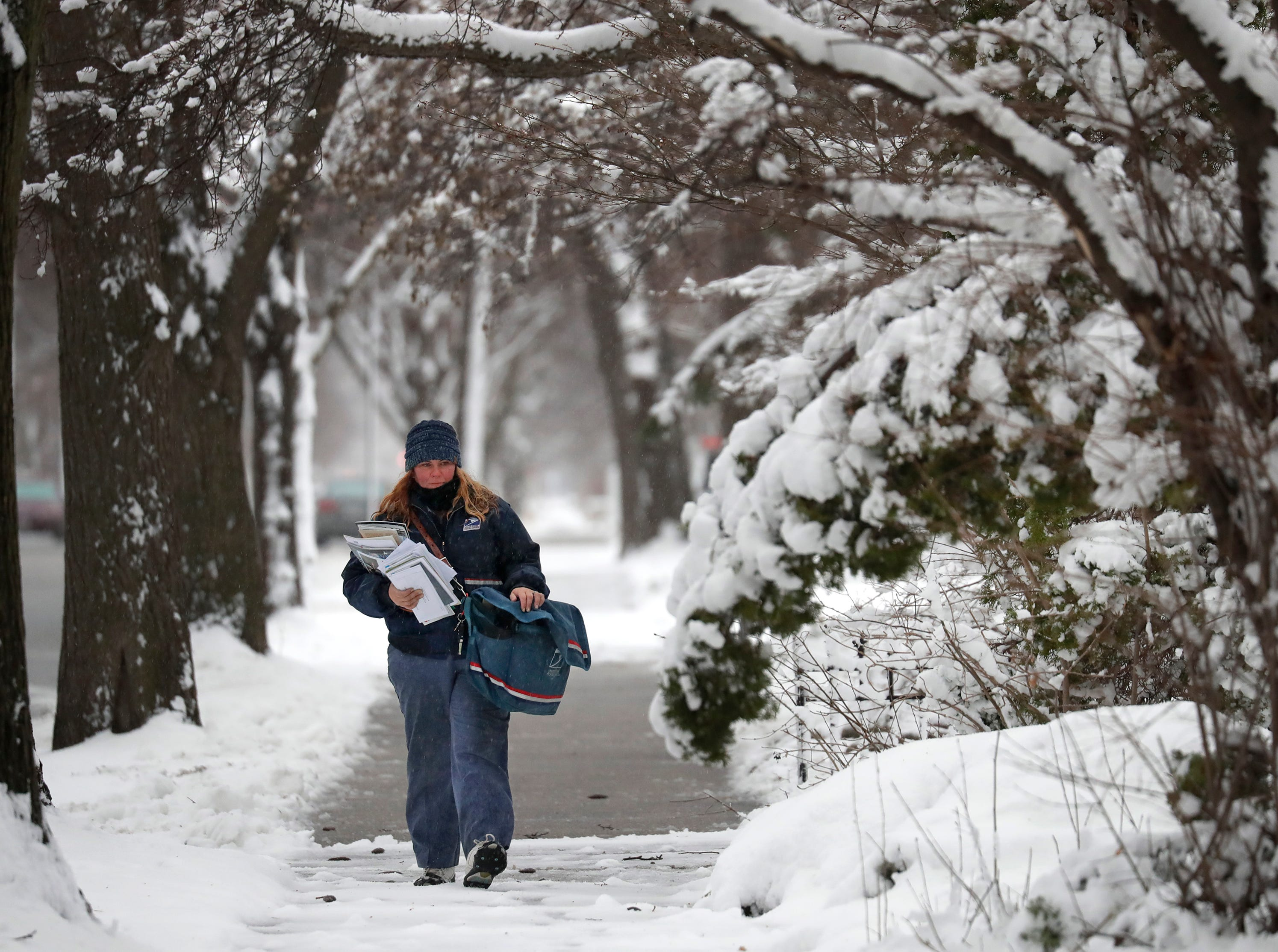 Ginny Klein, a city letter carrier assistant, delivers mail in windy sleeting conditions during a spring snow storm Thursday, April 11, 2019, in Oshkosh, Wis. Dan Powers/USA TODAY NETWORK-Wisconsin