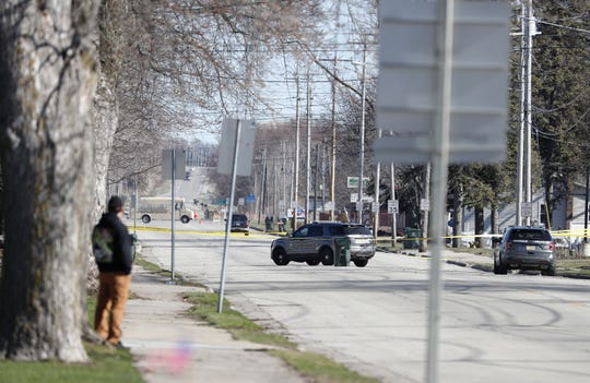 A man looks toward the 600 block of North Main Street in Seymour, where police found a 35-year-old man, a 4-year-old girl, and a 3-month-old girl dead after making entry to a home Friday because of a domestic disturbance call.