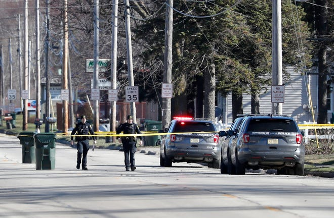 Police walk along the 600 Block of North Main Street where they received a domestic disturbance call and found a 35-year-old man, a 4-year-old female, and a 3-month-old female deceased after making entry to a home Friday, April 19, 2019, in Seymour, Wis.