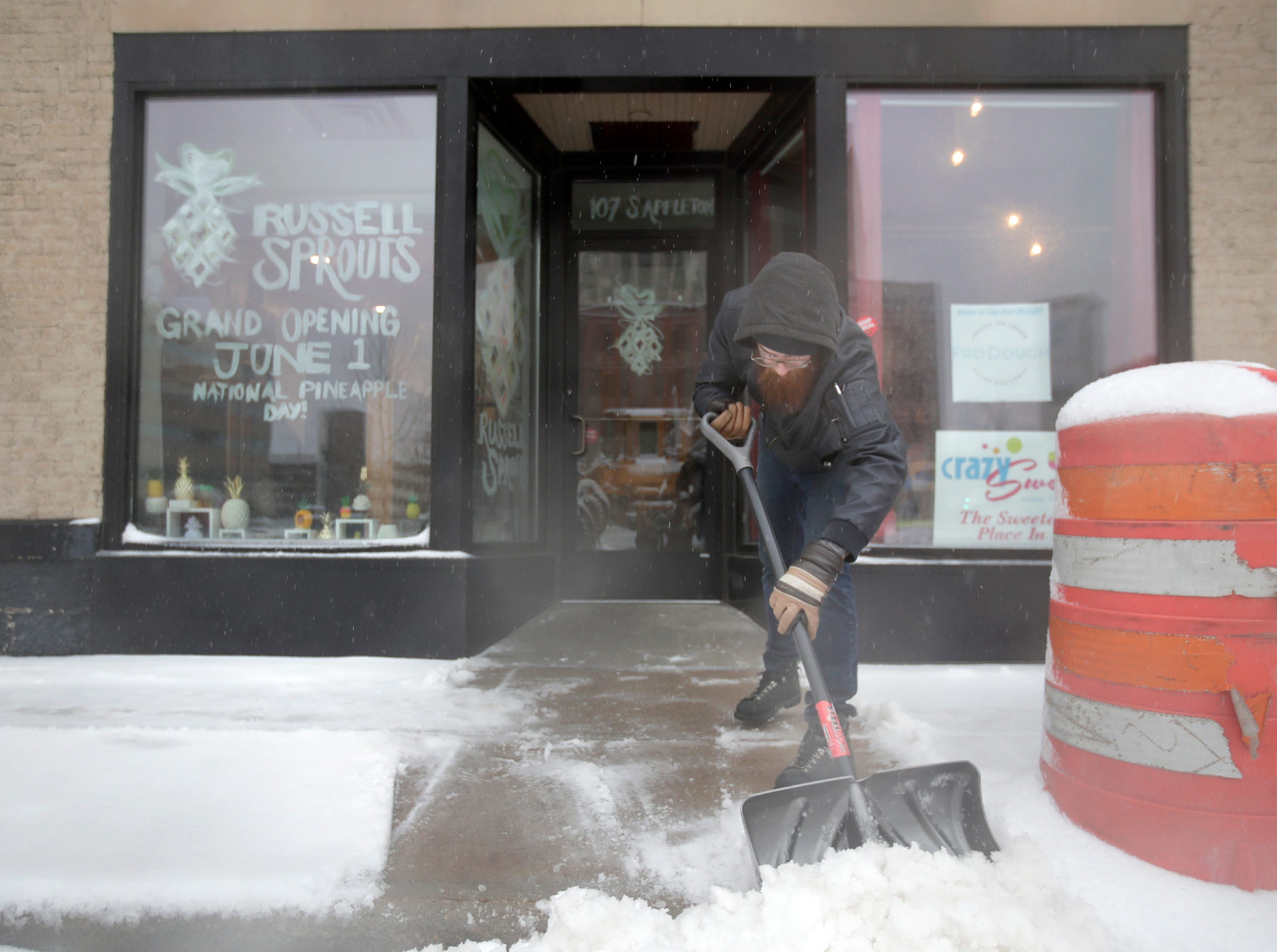 Maxwell Vanhandel, boyfriend of Russell Sprouts owner Carissa Hendricks, clears ice and snow from in front of the business in downtown Appleton Thursday, April 11, 2019, in Appleton, Wis. Russell Sprouts, a pineapple art gallery, opens on June 1.Danny Damiani/USA TODAY NETWORK-Wisconsin