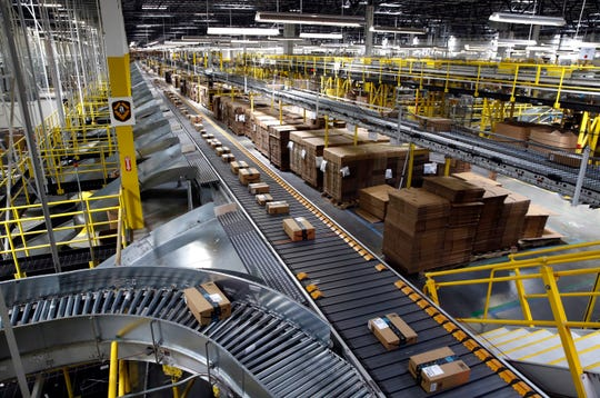 In this Aug. 3, 2017, file photo, packages ride on a conveyor system at an Amazon fulfillment center in Baltimore. Outside of ditching online shopping altogether, there are some small tweaks in how you shop that can cut down on the impact on the environment, such as slowing down shipping times and not filling up the cart with stuff you know you won't keep.