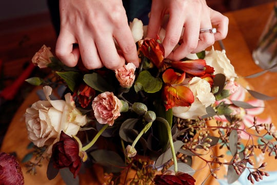 Liz Mally, who owns LPF Blooms, works on a centerpiece in her studio in her basement in Ferndale, Mich.