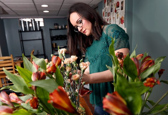 """Liz Mally, who owns LPF Blooms, works on a centerpiece in her studio in her basement in Ferndale, Mich. Mally learned there is misery in doing work purely for the sake of building a portfolio.  """"I was taking on pretty much any client I could get, regardless of budget or style, in hopes of gaining experience and getting my name out there,"""" said Mally."""