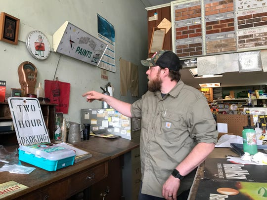 Jon Horn, manager of the ReClaim Madison, stands behind the counter inside the store.