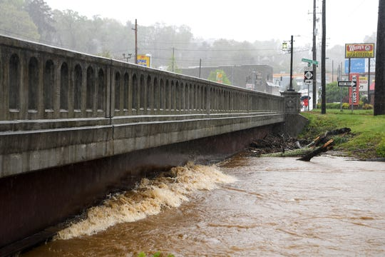 A wave is created as the Swannanoa River rises to meet the bridge over Biltmore Avenue in Biltmore Village before 2 p.m. on April 19, 2019.