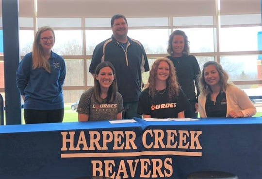 Harper Creek's Ashton Rowe signed to play lacrosse at Lourdes University in Ohio. She is joined by her high school lacrosse coaches and her parents.
