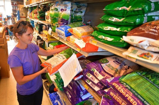 Lindsey Wilson, the garden center manager at Ace Hardware in Cocoa Beach, works in the fertilizer aisle at the store, which posts information for consumers on Brevard County's fertilizer use rules.