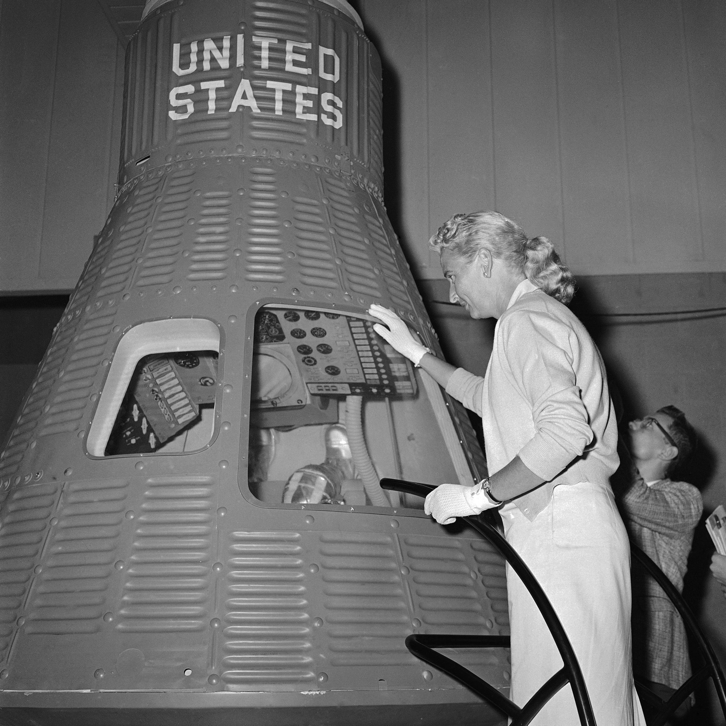 In this May 26, 1961, file photo, Jerri Cobb looks into a full-scale model of the Mercury capsule which carried Alan Shepard into space, in Tulsa, Okla.