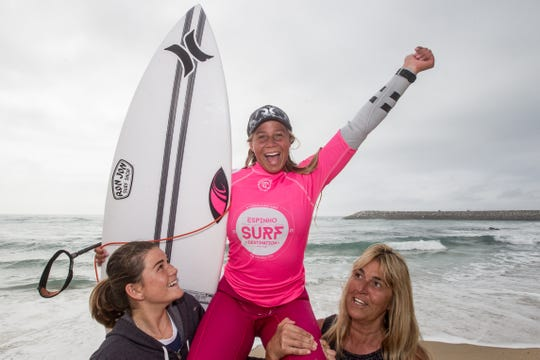 Rachel Presti of Melbourne Beach is carried off the beach after winning the first of two junior pro surf contests in Portugal.