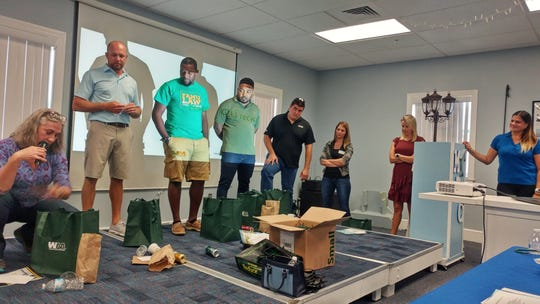 Members of a Leadership Brevard team look at examples of what can and can't be recycled.