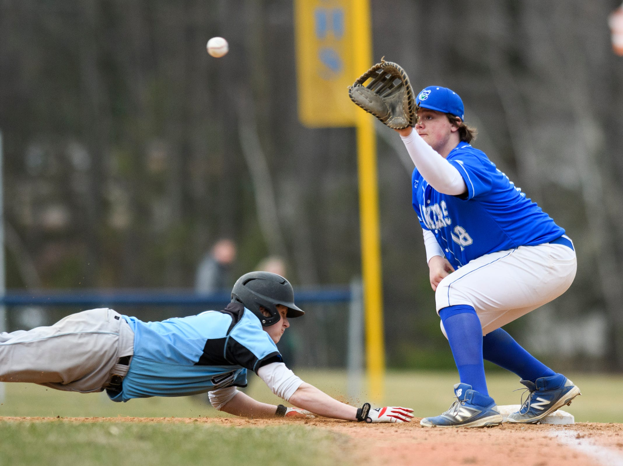 Colchester' first baseman Justin Dattilio (18) plays the ball on a pick off attempt during the boys baseball game between the South Burlington Wolves and the Colchester Lakers at Colchester high school on Thursday afternoon April 18, 2019 in Colchester, Vermont.