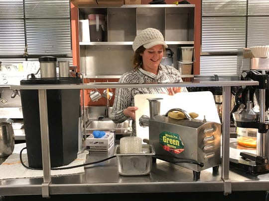 Melissa Cohen smiles behind the barista counter at Healthy Living Market & Cafe, April 3, 2019.