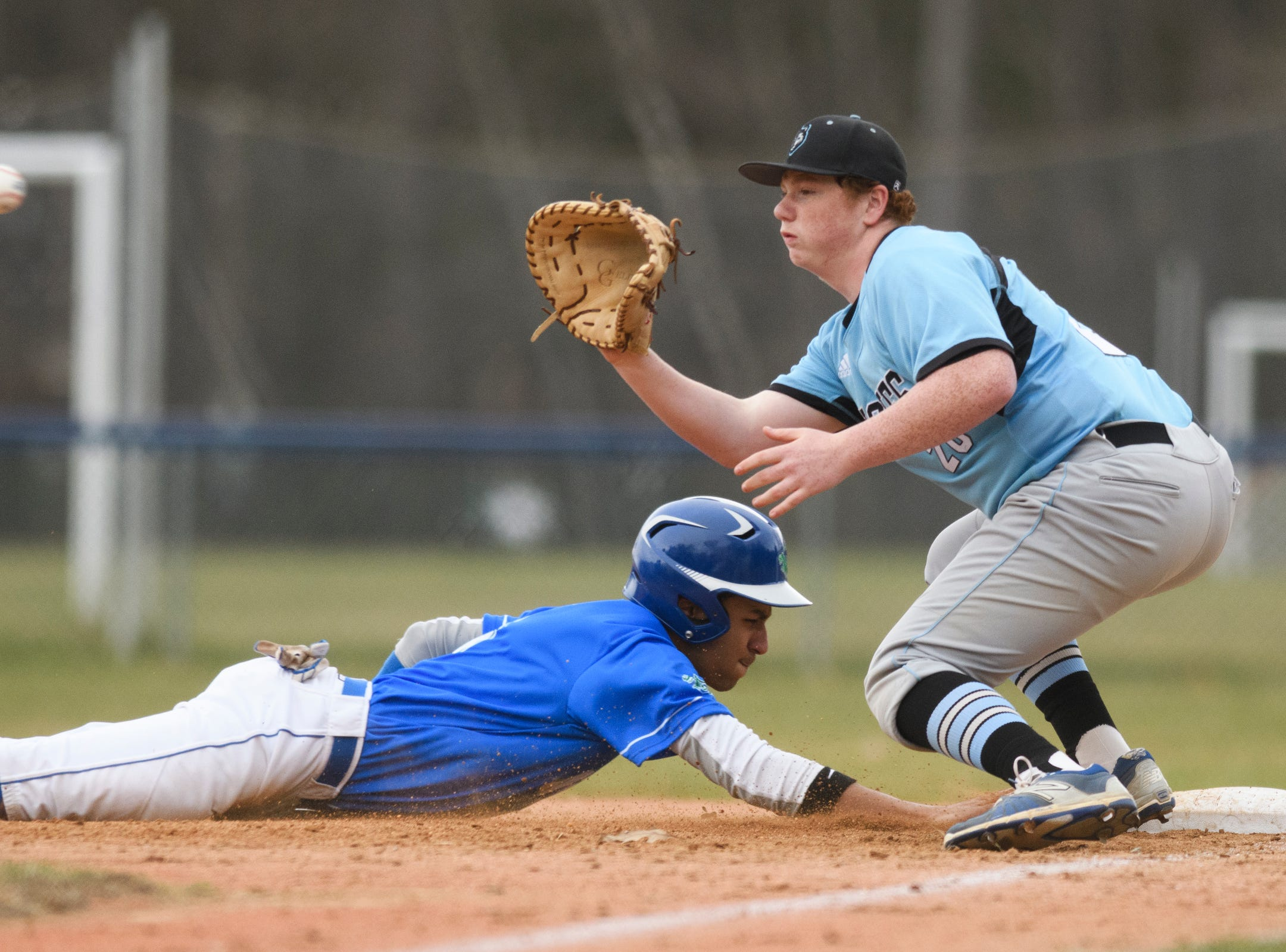 Colchester's Saul Minaya (3) dives to first as South Burlington's Ethan Moore (20) plays the pic off attempt during the boys baseball game between the South Burlington Wolves and the Colchester Lakers at Colchester high school on Thursday afternoon April 18, 2019 in Colchester, Vermont. (