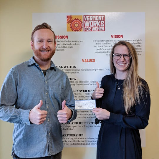 Dan White makes a donation to Vermont Works for Women, handing a check to Marketing Coordinator Romy Eberle.